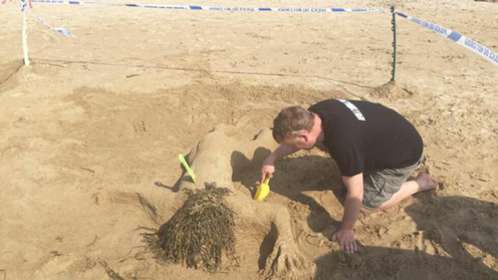 LIKNER ET ÅSTED: I konkurransen om å bygge den beste sandskulpturen, vant det lokale politiet i Cornwall-området i England. Etterpå måtte de beklage, fordi flere mente bidraget liknet et åsted. FOTO: TWITTER/TRURO POLICE