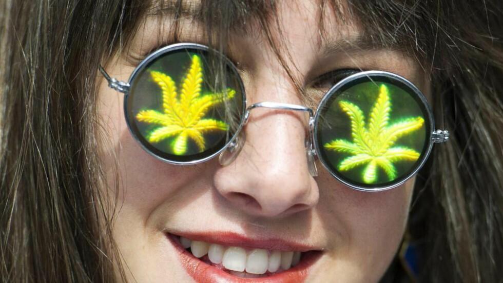 420-MARSJ: 20. april hvert år arrangeres demonstrasjoner verden over med krav om legalisering av marihuana. Denne kvinnen, som deltok i en «smoke off» i Toronto, Canada, kan kanskje få oppleve en liberalisering.. Foto Nathan Denette / The Canadian Press/  AP / NTB Scanpix