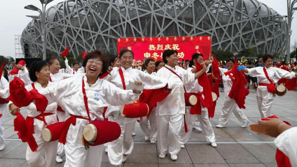 LEKENDE KINESERE: Jubel i Beijing etter at byen i dag ble tildelt vinter-OL i 2022. Foto: EPA/ROLEX DELA PENA/Scanpix