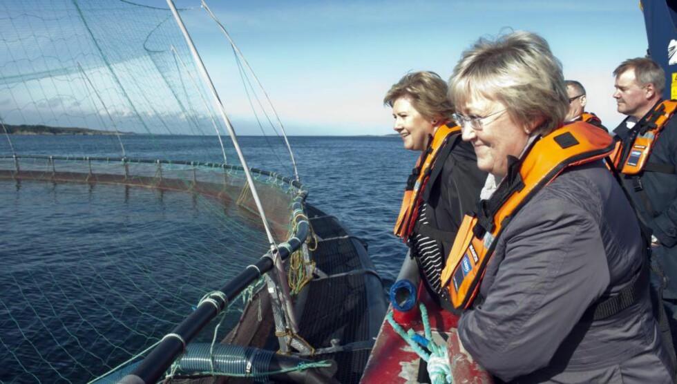 BLÅTT GULL: Statsminiser Erna Solberg (t.v.) og fiskeriminister Elisabeth Aspaker besøker et oppdrettsanlegg i Øygarden. Nå vil de mangedoble norsk lakseproduksjon. Foto: Marit Hommedal / NTB Scanpix