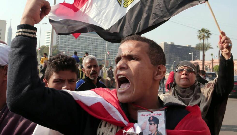 NYE DEMONSTRASJONER:  En mann pyntet med det egyptiske flagget og bilde av president al-Sisi under en demonstrasjon på Tahrir-plassen i Kairo nylig. Det har vært nye sammenstøt der med flere drepte og mange arresterte. Foto: EPA / NTB Scanpix
