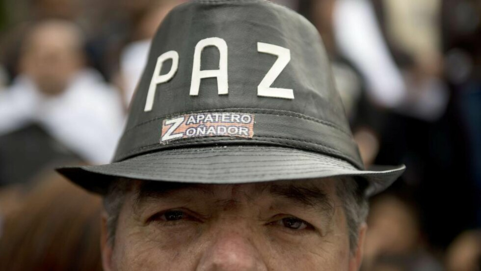 STØTTE TIL FRED: «Paz» - «fred» - står det på mannens hatt. På toårsdagen for fredsforhandlingene demonstrerte folk i gatene i Bogotá, samtidig som forhandlingene var i krise. FARC hadde tatt til fange en general og to medarbeidere. Men krisa løste seg raskt. Foto: AFP / Scanpix / Eitan Abramovich