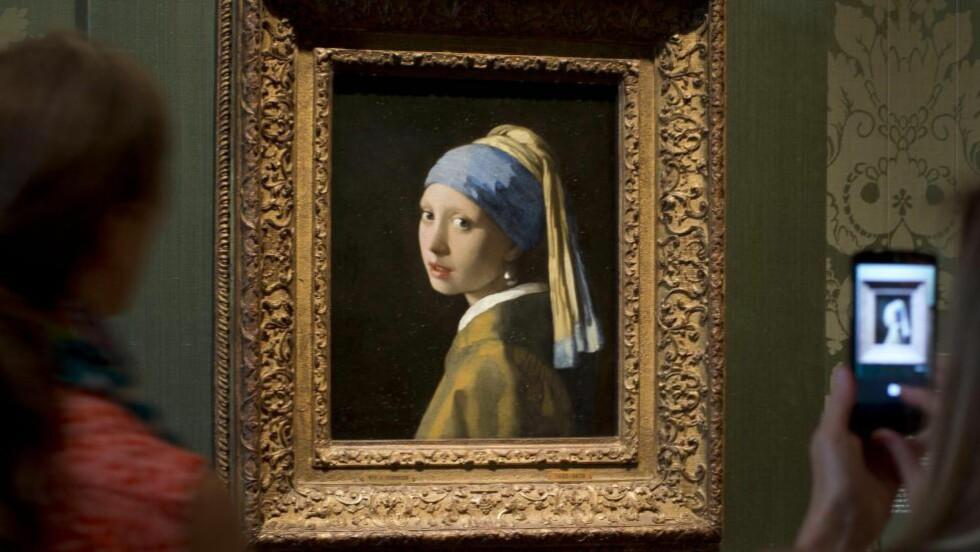 NORDENS MONA LISA: Besøkende på Mauritshuis i Den Haag svermer rundt Vermeers mesterverk «Pike med perleøredobb» fra 1665. Foto: Peter Dejong / AP / NTB Scanpix