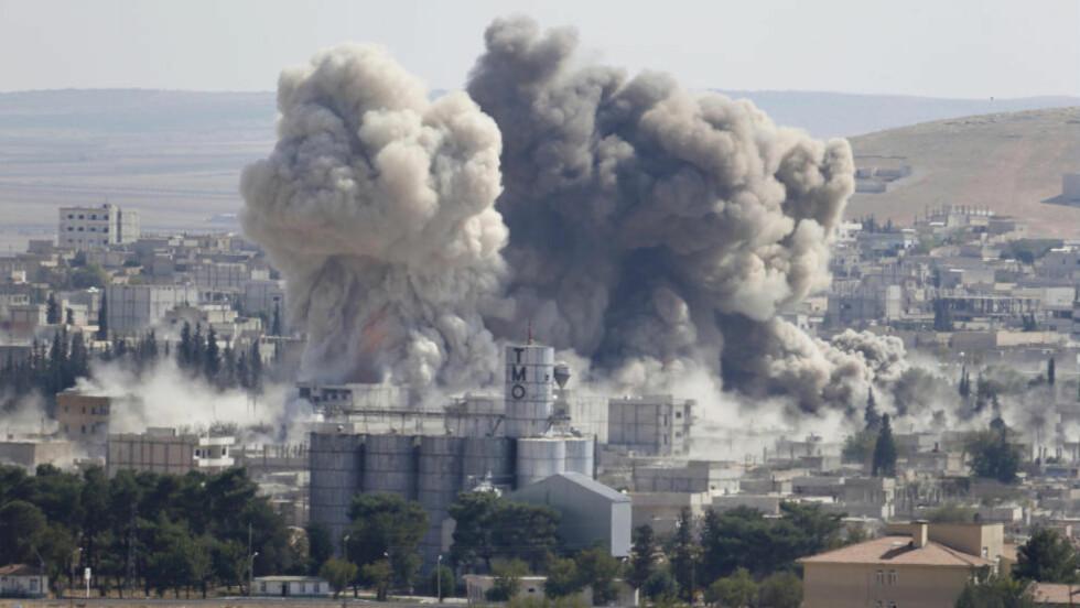 TYRKISK UTSYN: Røyken stiger etter et bombe-angrep mot stillingene til IS i den syriske grensebyen Kobani. Mulig kommer de kraftige bombetoktene litt for seint til å hjelpe de kurdiske krigerne som forsvarer byen. Og bak grensegjernet sitter de tyrkiske styrkene og ser på mens slaget utvikler seg. Foto: REUTERS / Scanpix / Umit Bektas