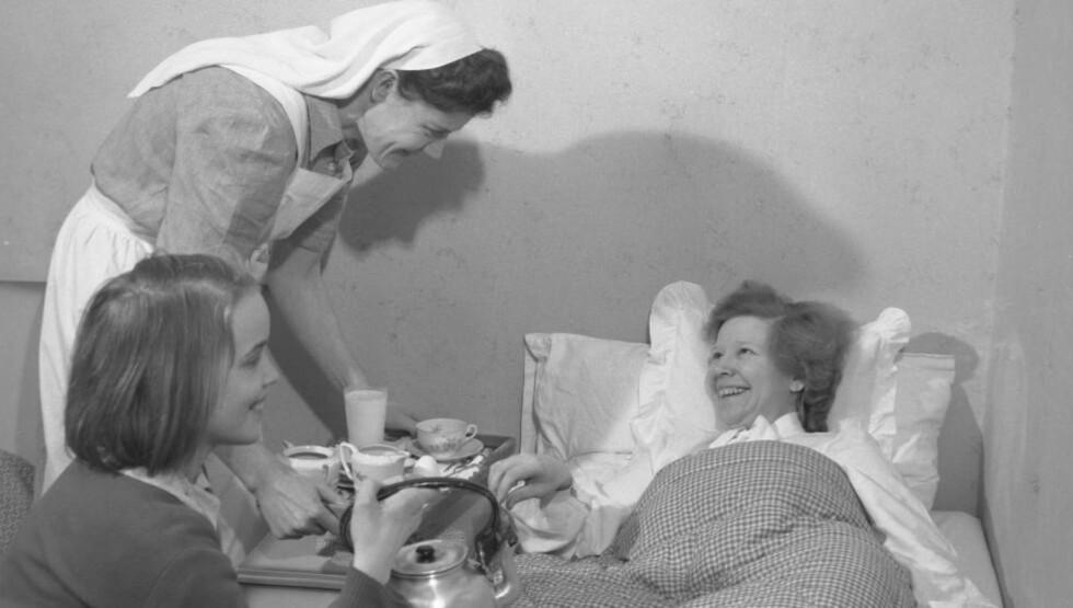 SLIK VAR DET: Husmorvikar var en god hjelp å få når mor var syk. Her husmorvikaren Solbjørg Slotvik, i uniform, hos familien Gulbrandsen i 1950. Eldstedatteren Reidun hjelper til å servere kaffe til mor.  Foto: NTB / Scanpix