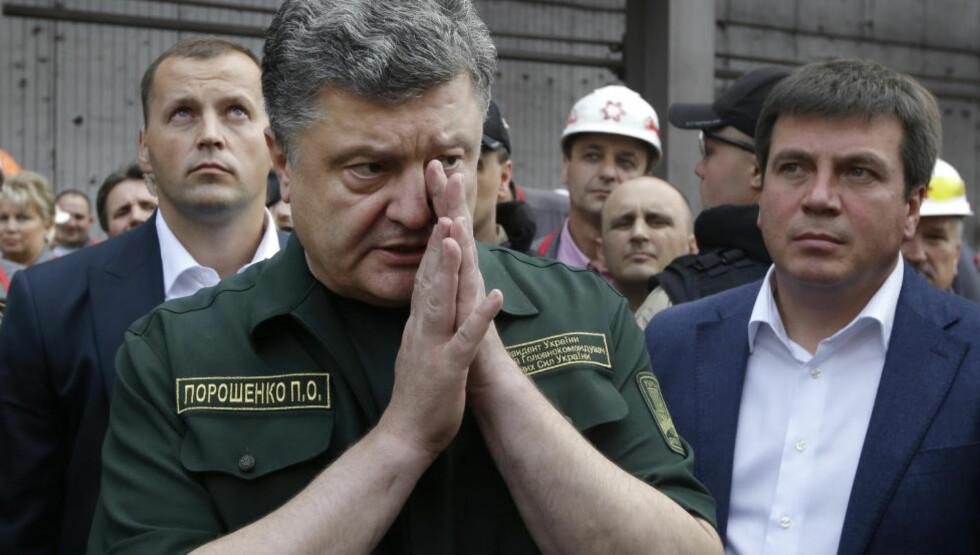 RUSK I ØYET? Eller en bønn til høyere makter? Ukrainias president Petro Porosjenko har uansett mer enn rusk i øyet, og all grunn til å be til høyere makter. Foto: Sergei Grits / AP / NTB Scanpix