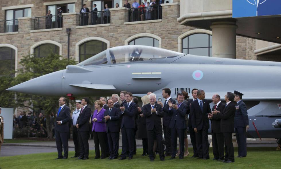 TRENGER HJELP: NATO-lederne foran en modell av et jagerfly klapper for virkelige jagerfly i lufta over Cardiff under toppmøtet. De innser at de bare er fra lufta de kan krige mot ultra-islamistene i Irak of Syria. På bakken trenger de hjelp. Foto. AP / Scanpix / Matt Dunham