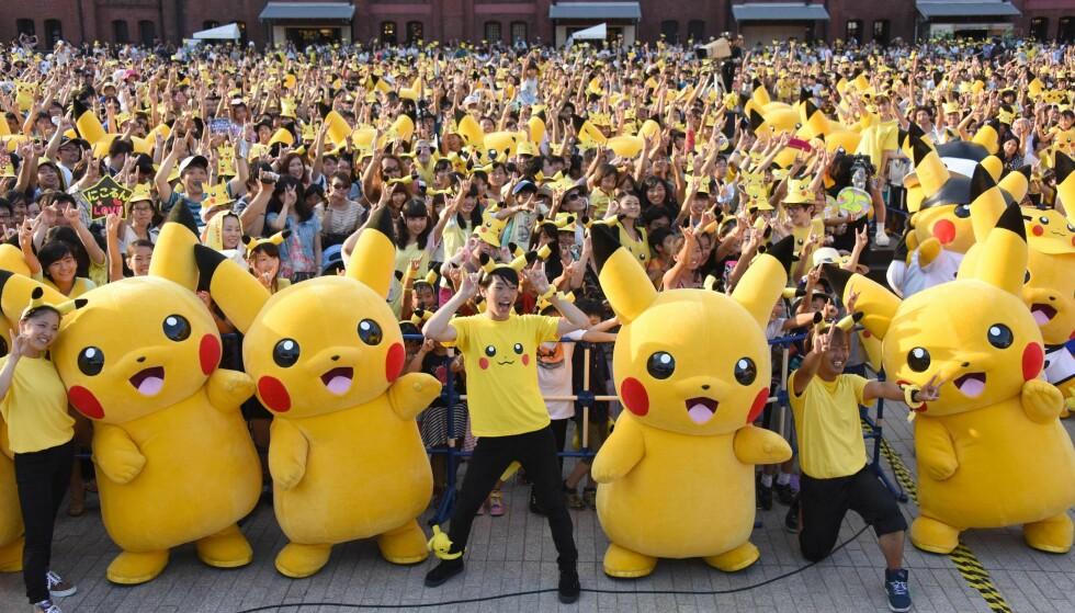 ENORM INTERESSE: Mobilspillet Pokémon Go har tatt verden med storm. Her er et titals mennesker kledd opp som den kjente Pokémon-karakteren Pikachu i Tokyo. Foto: Toru Yamanaka/AFP/NTB Scanpix
