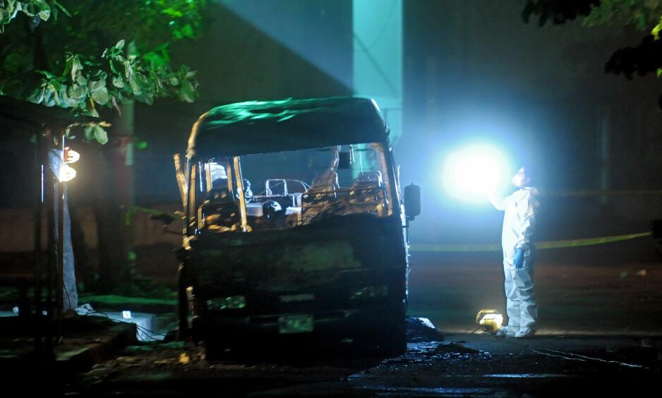 En politietterforsker i Mejicanos, nord for San Salvador, tar bilder av en buss som Barrio 18-medlemmer skal ha satt fyr på. Bussbrannen krevde elleve menneskeliv. Foto: AFP Photo / NTB Scanpix