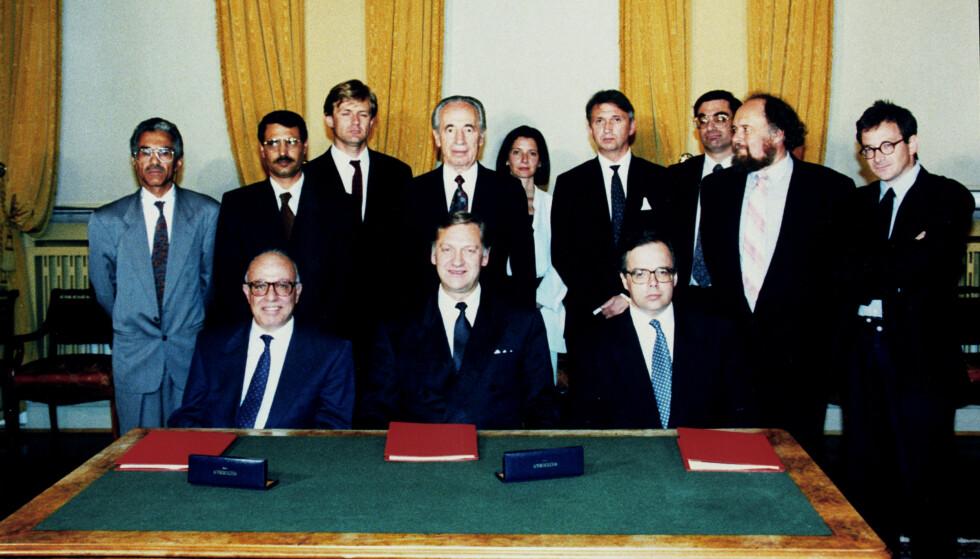 HEMMELIGE FORHANDLINGER: Hovedaktørene bak den første Oslo-avtalen fotografert i Parkveien 45 i Oslo 20. august 1993. I midten ved bordet sitter tidligere utenriksminister Johan Jørgen Holst, og rett bak seg har han Israels daværende utenriksminister Shimon Peres. Holst er flankert av den israelske forhandlingslederen Uri Savir (til høyre) og hans palestinske motpart Abu Ala. Bak Peres står de tre norske diplomatene som var mest aktive i de hemmelige forhandlingene i Norge i 1993; Statssekretær Jan Egeland, Mona Juul og hennes mann Terje Rød-Larsen. Foto: Overvåkingspolitiet / NTB scanpix