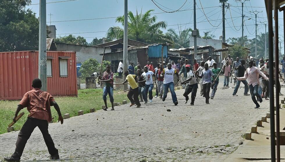 IMBONERAKURE: Ungdomspartiet, en slags paramilitær ungdomsfløy av Burundis regjeringsparti, beskyldes for å gjengvolda familiemedlemmer av sine politiske motstandere. Her fra en demonstrasjon i mai i 2015. I forgrunnen står en mann som demonstrerer mot regjeringspartiet. Imbonerakure-medlemmer kommer løpende mot ham, bevæpnet med kjepper. Foto: AFP Photo / NTB Scanpix