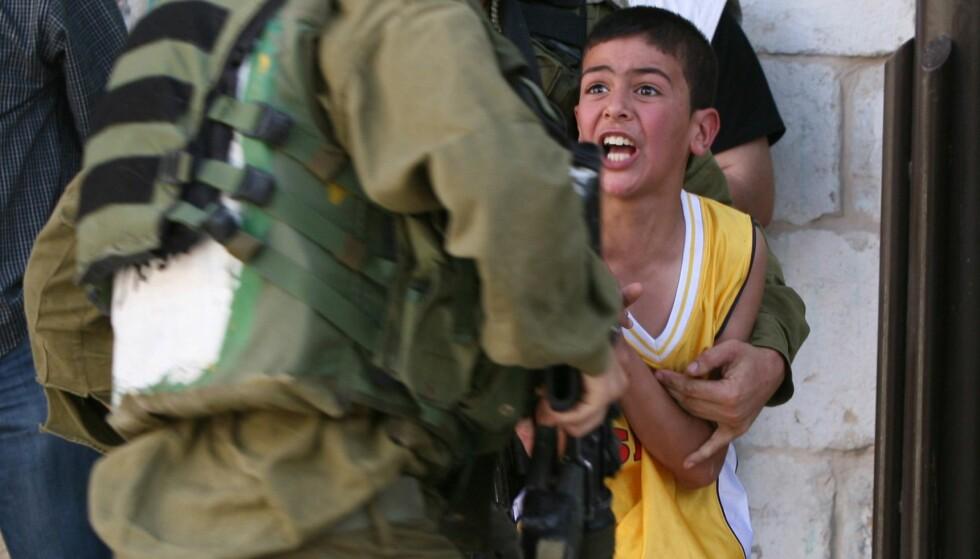 TATT: En palestinsk gutt blir anholdt av israelske soldater etter å ha kastet stein mot jødiske nybyggere i Hebron på Vestbredden. Arkivfoto: AFP/Scanpix NTB