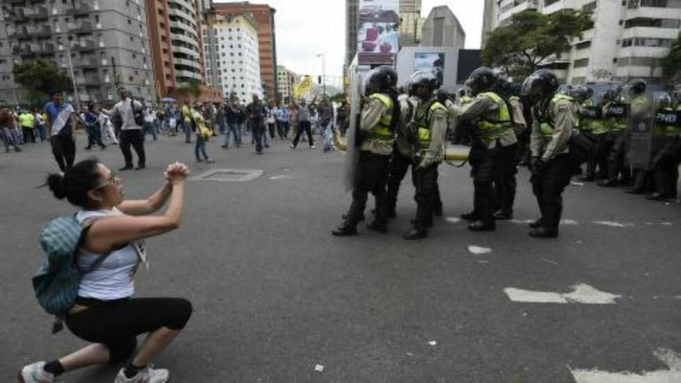 EN BØNN: En kvinne kneler foran politifolk i Caracas i dag. Sivilbefolkningen i landet lider under mangel på vann, mat, elektrisitet og medisiner. Foto: AFP PHOTO / JUAN BARRETO