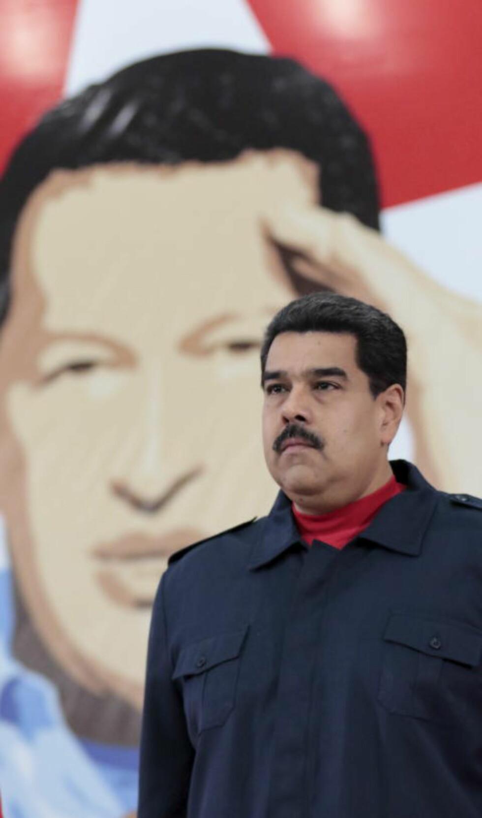I CHAVEZ' SKYGGE: Venezuelas president Nicolas Maduro foran et portrett av Hugo Chavez. Chavez var stort sett en populær president fra han tiltrådte i 1999 fram til han døde i 2013. Etterfølgeren Maduro har aldri vunnet folkets gunst. Foto: REUTERS/Miraflores Palace