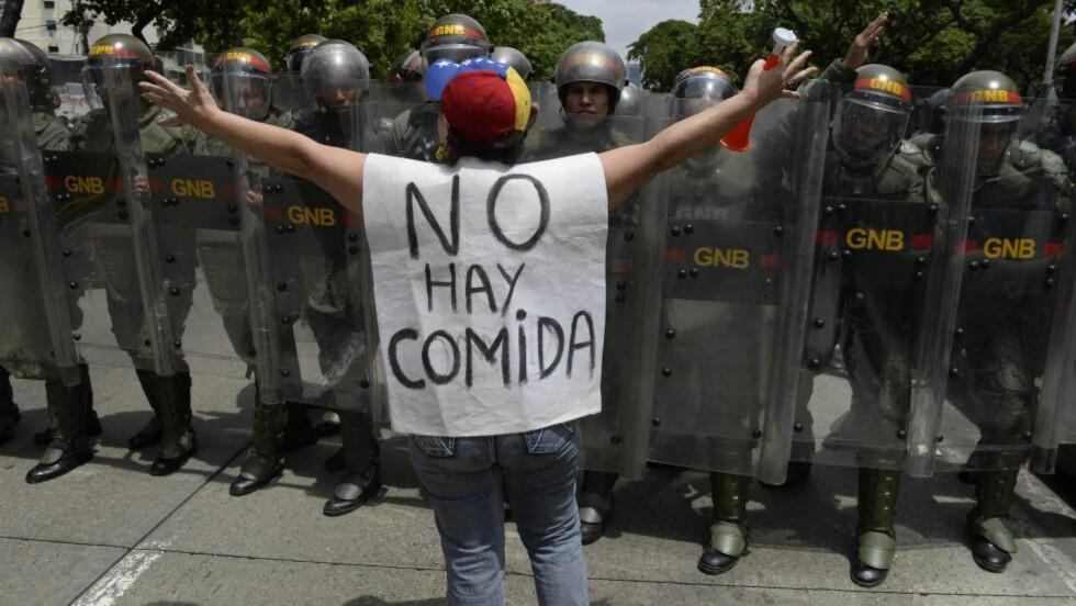 IKKE MAT: En kvinne bærer et plagg med påskriften «Det finnes ikke mat» under en demonstrasjon mot de utvidede fullmakter president Nicolas Maduro har innvilget seg som følge av unntakstilstanden han erklærte 14. mai. Foto: AFP PHOTO / FEDERICO PARRA