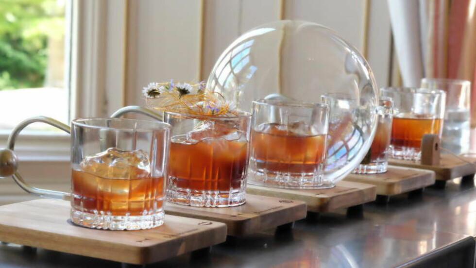 FEM GYLNE SANSER: Spanske Antonio presenterte fem glass på hjemmelagde treplater med sansesymbolene brent ned i treverket. Hvert glass skulle appelere til en ny sans. Foto: HELLE ØDER VALEBROKK