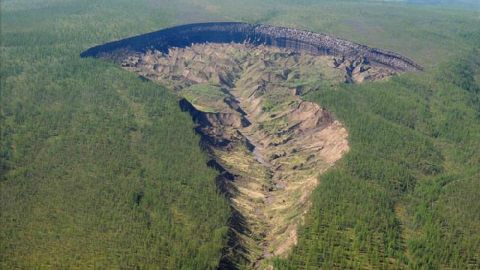 KRATER: Batagayka-rateret, som på folkemunne har fått tilnavnet «Porten til underverdenen», er omlag en kilometer langt og 90 meter dypt. For 25 år siden eksisterte det ikke, og hvert år blir det 20 meter bredere. Det skremmer både de lokale innbyggerne og forskerne. Foto: Alexander Gabyshev / NEFU Research Institute of Applied Ecology of the North
