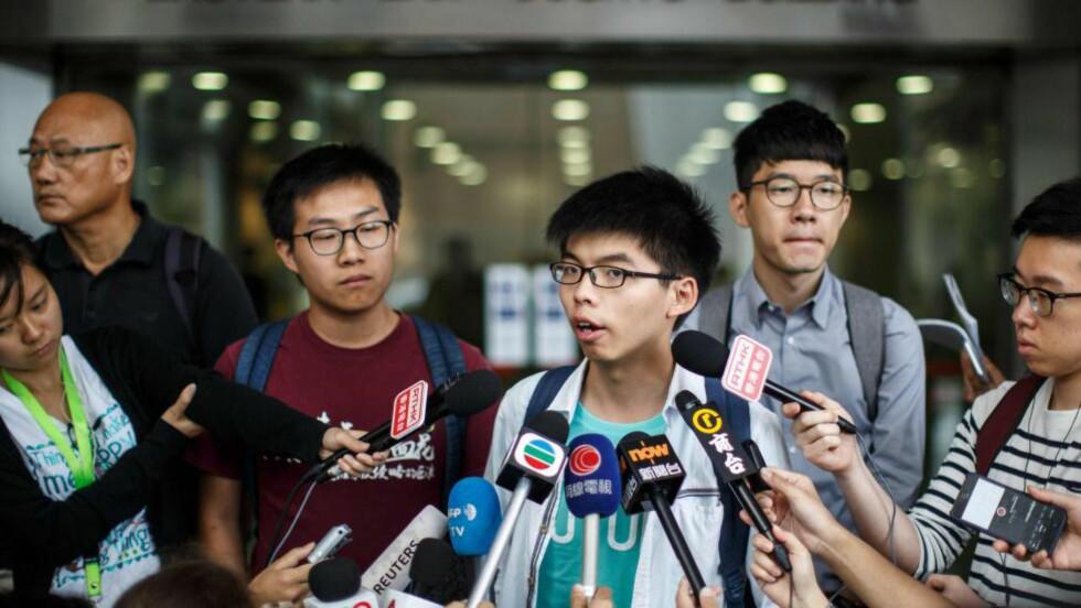FRIFUNNET:  Studentlederen Joshua Wong (i midten) utenfor retten i Hongkong etter at han ble frifunnet tirsdag. Foyo: ANTHONY WALLACE, AFP/NTB Scanpix.