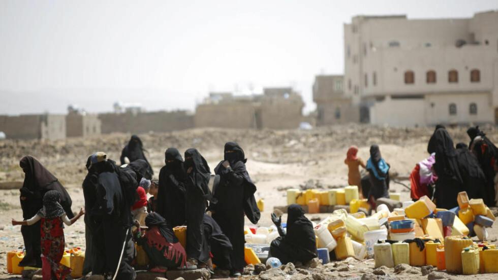 BLODIG BORGERKRIG: Kvinner og barn fyller vann i kanner fra en offentlig tappestasjon like utenfor Jemens hovedstad Sanaa. Foto: Hani Mohammed / Ap / NTB Scanpix