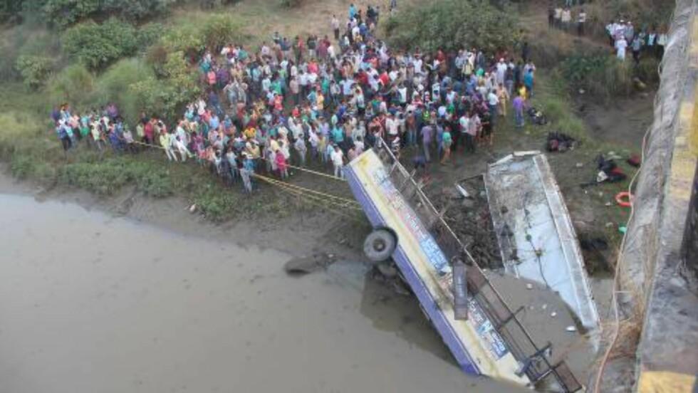 TAKET LØSNET:  Redningsmannskap og tilksuere prøver å trekke bussen opp fra elva. Foto: AFP/NTB Scanpix.