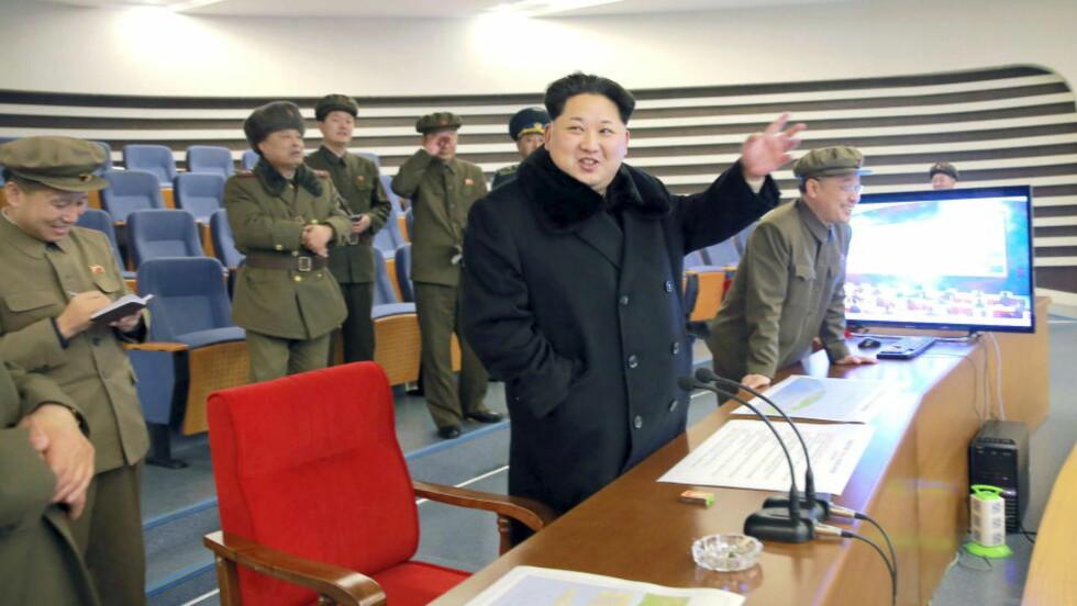 SMILENDE: Raketten, som nordkoreanerne i natt sendte opp, blir i landets medier beskrevet som en gave av lojalitet til landets unge leder, Kim Jung-un. Her følger han selv med på oppskytingen, fra et kontrollrom. Foto: Kyodo/Reuters / Scanpix