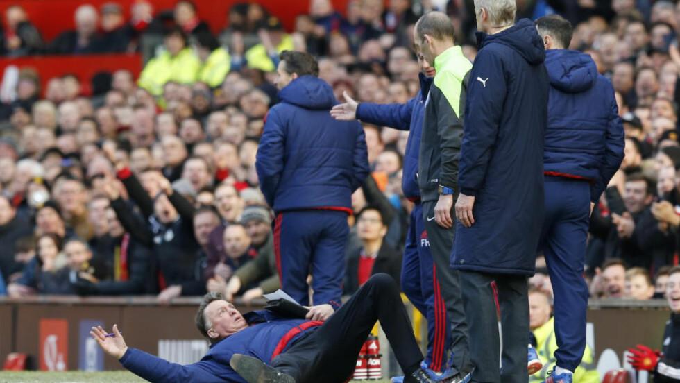 MERKELIG OPPFØRSEL: Fjerdeommer Mike Dean skjønte nok lite da Louis van Gaal plutselig kastet seg ned foran ham. Foto: Reuters / Phil Noble / NTB Scanpix