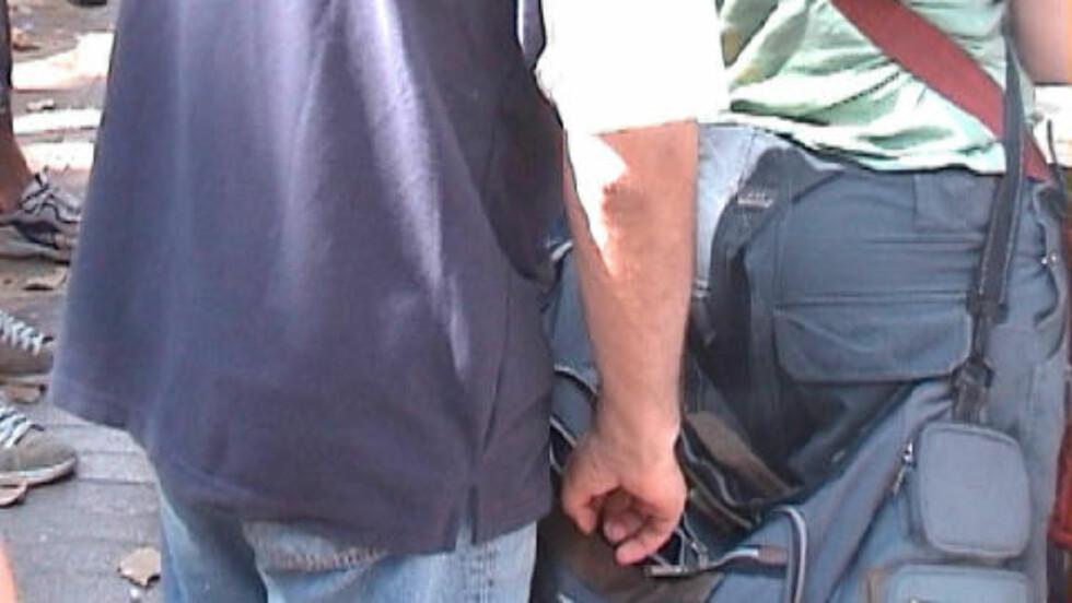 I AKSJON: En lommetyv på vei opp i veska til et intetanende offer. Foto: Bob Arno