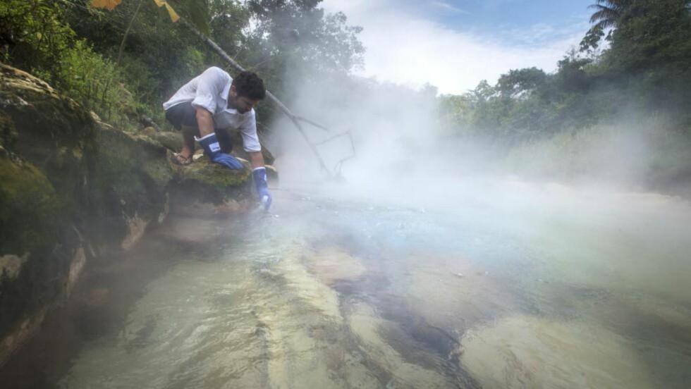 TJUKKE HANSKER: Andrés Ruzo har selv forsket på det varme vannet i elva i Amazonas. Hans teknikk er å holde seg lavt, for balansens skyld. Sandaler og shorts er egentlig ikke perfekt påkledning, men den lokale sjamanen ba han bruke føttene som øyne. Så langt har han unngått uheldige besøk i vannet. Foto: Devlin Gandy