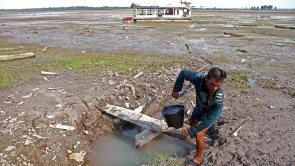 HENTER VANN: Denne mannen henter vann fra en brønn i den tørrlagte innsjøen Do Aleixo i nærheten av Manaus. Bildet ble tatt i oktober 2015. Foto: Raimundo Valentim / EPA / NTB Scanpix