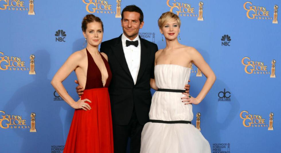 KOLLEGAER:  Amy Adams (t.v) og Jennifer Lawrence (t.h) måtte godta å få mindre betalt enn sine mannlige medskuespillere i filmen «American Hustle» fra 2013. Her med Bradley Cooper som hadde en av hovedrollene i filmen. Foto: Scanpix