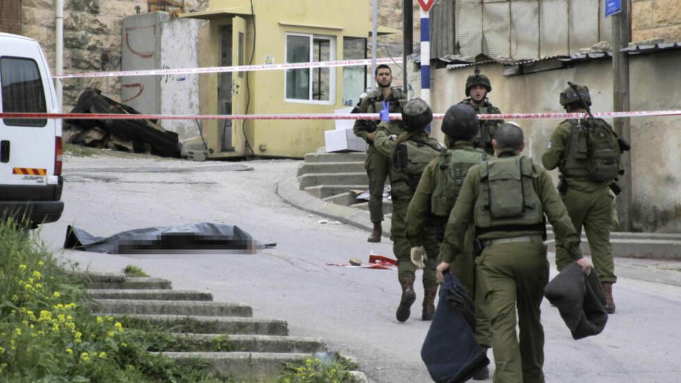 LIGGER DØD I GATA: Israelske soldater vokter liket til en drept palestiner i Hebron på Vestbredden. Et dødsfall som har satt sinnene i kok i Isral. Foto: NTB Scanpix