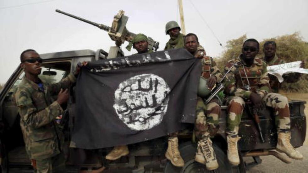 TERRORFLAGG: Nigerianske soldater med et Boko Haram-flagg de fant i Damasak da de inntok byen i mars 2015. Foto: Emmanuel Braun/Reuters