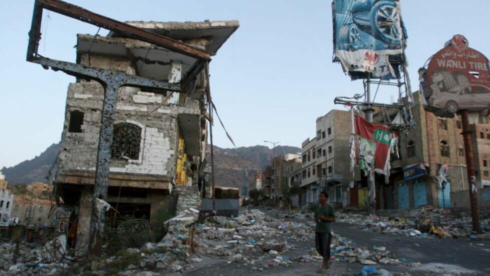 KRIGSSONE:  En mann går forbi et av de mange husene i Jemen som er ødelagt i forbindelse med den pågående krigen i landet. Saudi Arabia og De forente arabiske emiratene fører krig i landet, og Norge fortsatte å selge våpen til de to landene i fjor, til tross for motstand blant en rekke norske grupper og organisasjoner. Frykten er at norsk militært utstyr kan bli brukt i krigen. Bildet er fra den sørvestlige byen Taiz. Foto: Anees Mahyoub / Reuters / Scanpix