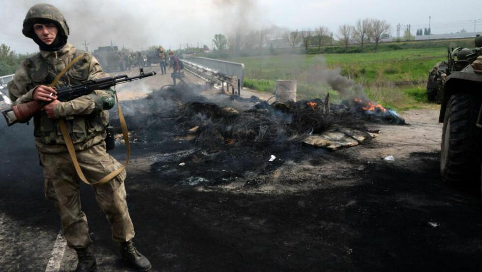 KRIG: I april, mai og juni 2014 herjet krigen i Ukraina som verst. Her er en ukrainsk soldat ved en kontrollpost i et område som de rykket inn i samme morgen, like ved den sørlige byen Slavyansk. Bildet er tatt 2. mai 2014. Foto: Vasily Maximov/AFP