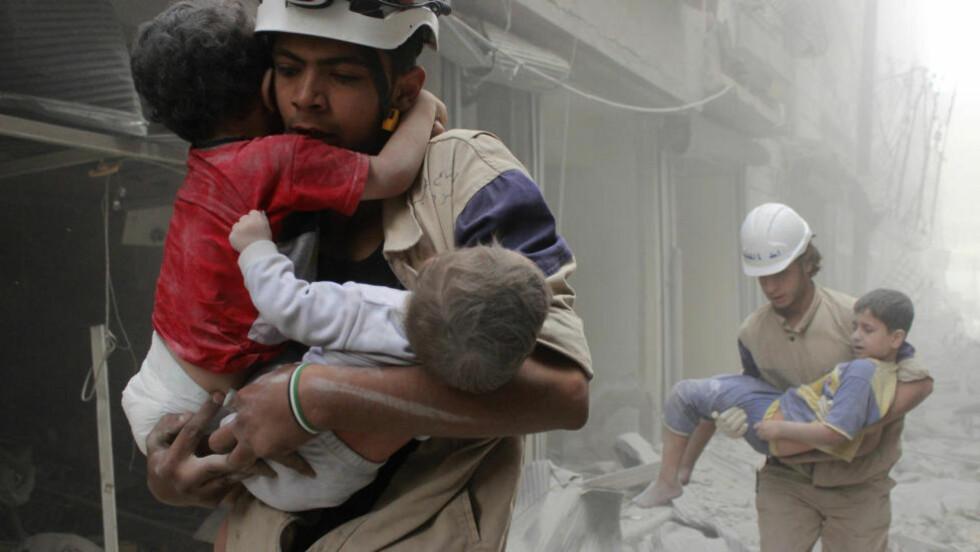 BLODIG KRIG:  Over 250 000 mennesker har mistet livet i løpet av de snart fem årene som den syriske krigen har vart. Nå er situasjonen for de sivile i landet om mulig enda verre, med bombing fra stadig flere parter. Her blir barn hjulpet ut fra et nabolag i Aleppo, etter at Bashar al-Assads styrker bombet området i fjor. Foto: Sultan Kitaz / Reuters / Scanpix