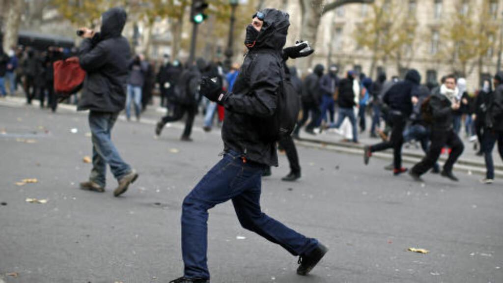 TROSSET FORBUD: En demonstrant kaster gjenstander mot opprørspolitiet under sammenstøt i Paris søndag. Foto: Benoit Tessier / Reuters / NTB scanpix