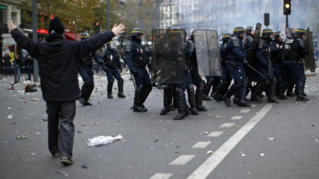 SKJOLD OG TÅREGASS: En miljøaktivist går mot politiet på Place de la Republique, der de planlagte demonstrasjonene er avlyst etter terrorangrepene for drøye to uker siden. Politiet skal ha brukt tåregass for å spre demonstrantene. Foto: Benoit Tessier / Reuters / NTB scanpix