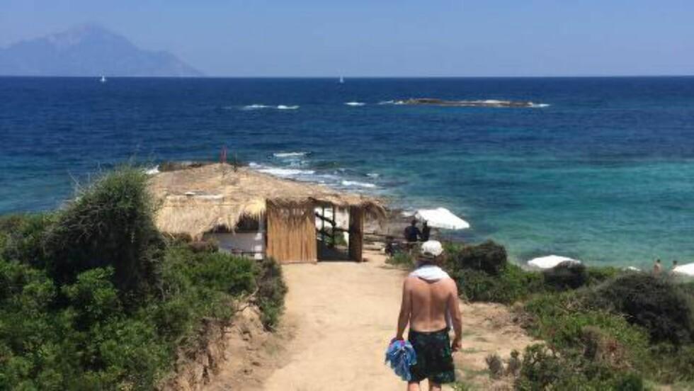 STRANDLIV: En av de mange små strendene på Sithonia, som nettopp har fått bygget ut en liten strandbar. I horisonten skimtes toppen av Athos-fjellet. Foto: HILDE MARIE TVEDTEN