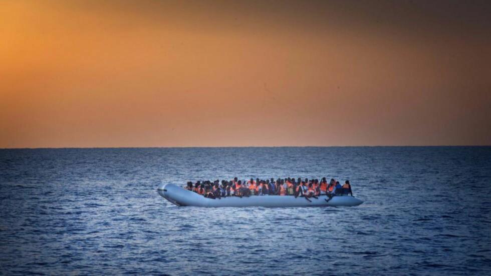 """OVER HAVET: Dette bildet er tatt under en reportasje i Middelhavet med det norske fartøyet """"Siem Pilot"""" på søking etter flyktninger. Under kveldssola dukket denne overbelastede båten opp. FOTO: STIG B. HANSEN"""