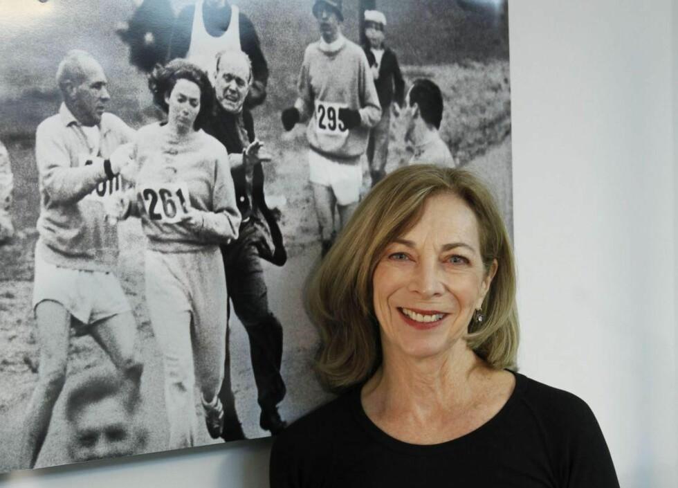 EVIG AKTUELT: Kathrine Switzer i Spania i 2014 foran det historiske bildet fra Boston maraton i 1967. Selv om bildet snart er 50 år gammel, så preger det fortsatt livet og karrieren til Switzer. Bildet endret både hennes og millioner av andre kvinners liv, som følge av at det satte fart i likestillingen innen idretten. Foto: Chema Moya / EPA / NTB Scanpix