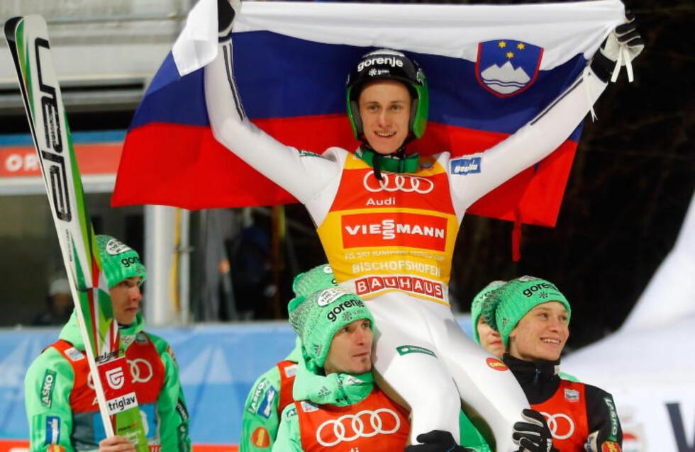 KONGEN: Peter Prevc vant både kveldens renn og hoppuka sammenlagt. Her hylles han av sine slovenske lagkompiser. Foto: REUTERS / Dominic Ebenbichler / NTB Scanpix