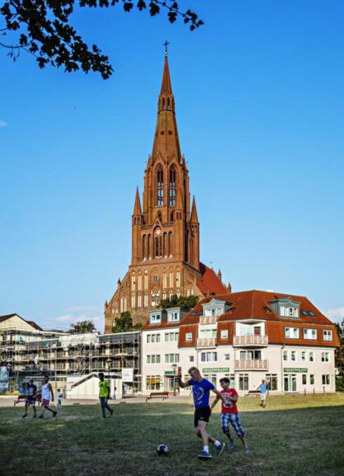 DAGENS GJØREMÅL: Med Bartolomeukirken som vitne, spiller byens ungdommer fotball.