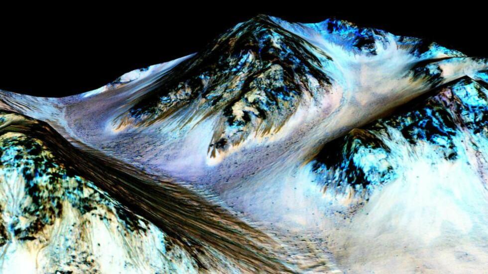 VANN PÅ MARS:  De mørke stripene til Mars sine fjell er områder Nasa sier de har funnet flytende vann. - Vi har ikke hatt det bevis for det før nå, sa panelet mandag. Alfred McEwen presiserer at vannet ikke er stabilt, i og med at temperaturene på Mars er svært kalde. Foto: Demotix Live News/Demotix/Corbis