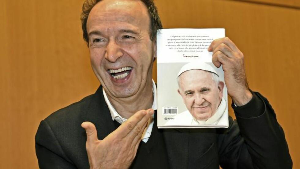 KJENDISVENNER: Den italienske skuespilleren og regissøren Roberto Bengini var på boklanseringa tirsdag 12. januar. Han har medvirka til boka. Bak på boka ser vi en smilende pave. Foto: AFP, NTB Scanpix