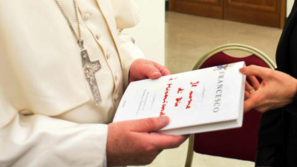 SAMTALE MED JOURNALIST: Boka, som på norsk har fått tittelen «Guds navn er barmhjertighet», er snart på markedet. Den beror på en samtale paven hadde med journalisten Andrea Tornielli. Her får paven en kopi av forlagssjef Marina Berlusconi. Hun er datter av Silvio Berlusconi. Boka er Frans sin første og skal publiseres i 86 land. Foto: NTB Scanpix, AFP