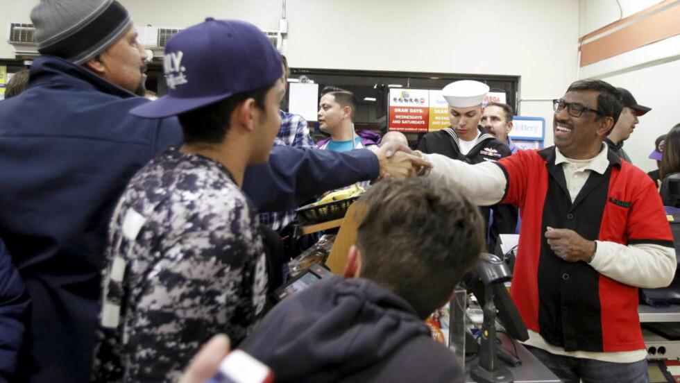 SOLGTE LODDET: Det var god stemning i 7-11-kiosken til M. Faroqui, hvor vinnerloddet ble solgt. Foto: REUTERS / Alex Gallardo / NTB scanpix