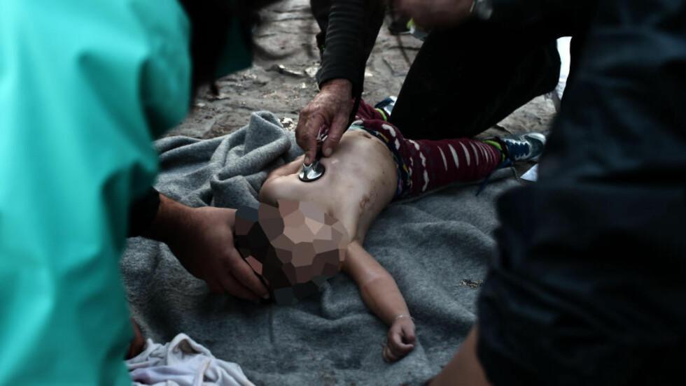 GJENOPPLIVNING:  Redningsarbeidere på stranda i Lesvos utførte i dag livreddende førstehjelp for å prøve å vekke denne gutten til live igjen, etter at båten han satt i sank på vei fra Tyrkia til Lesvos. Det er uklart om gutten overlevde, eller om han er en av de barna som døde i dag. Over fire båter skal i dag ha kantret på havet. Foto: NTB Scanpix / AFP PHOTO / ARIS MESSINIS