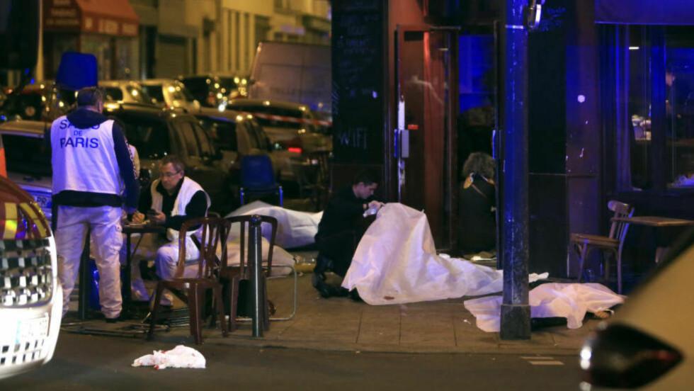 DUKER OVER DE DREPTE: Døde personer lå tildekket utenfor restauranten Le Carillon. Foto: Thibault Camus / AP / NTB Scanpix