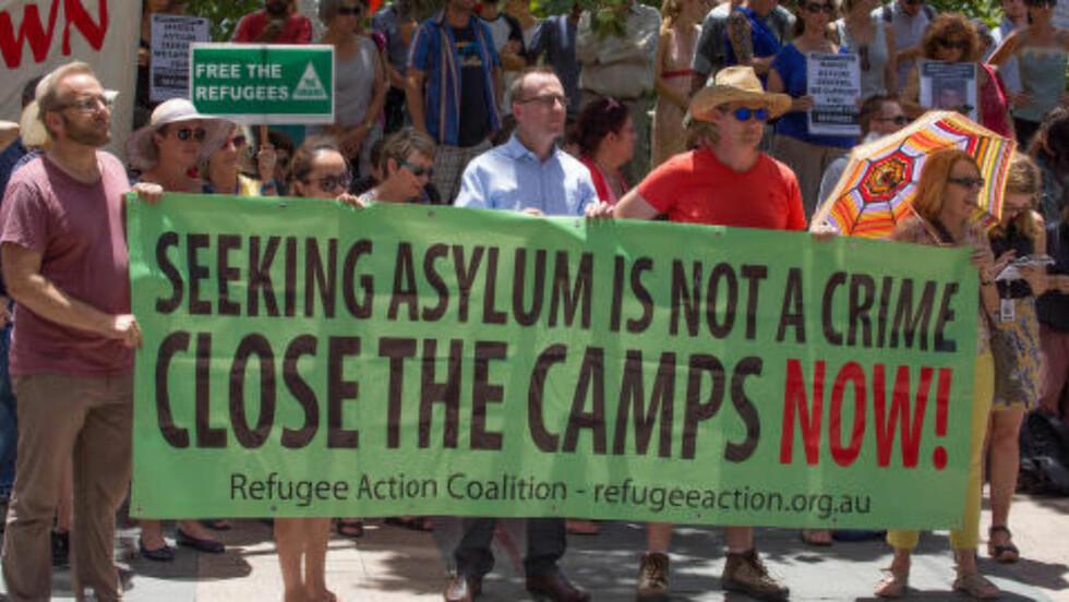 PROTESTERER: Protestanter i Sydney bærer bannere med et klart budskap: - Å søke asyl er ikke kriminelt. Steng leirene nå! mener menneskerettighetsorganisasjonen Refugee Action Coalition. Foto:  Richard Ashen / Demotix / NTB Scanpix