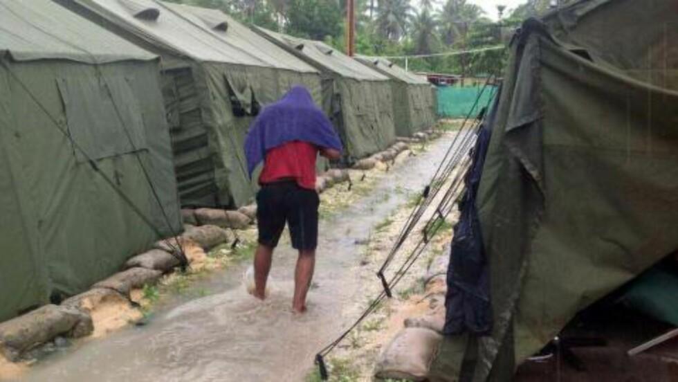 DÅRLIGE FORHOLD: Et udatert bilde viser en mann som går mellom teltene i asylsøkerleiren på Manus Island i Papua Ny-Guinea. Foto: AFP Photo / Refugee Action Coalition / NTB Scanpix